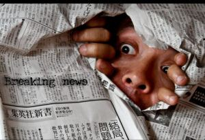 Face peeping through a newspaper