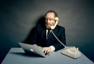 Business man on his laptop with a phone strapped to his ear